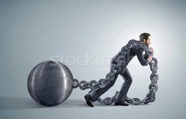 Tired businessman dragging heavy chains Stock photo © konradbak