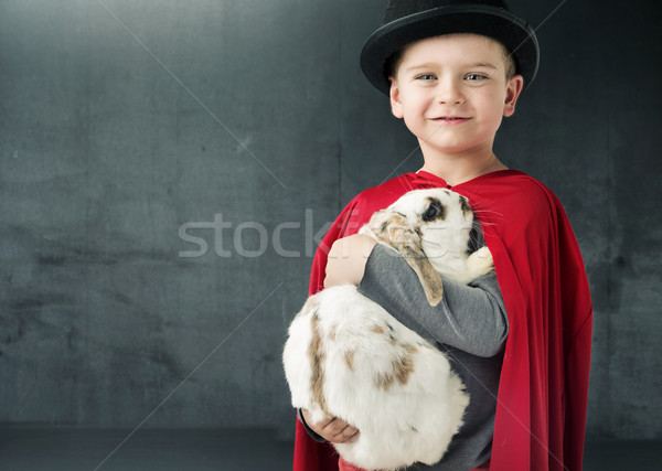 Little illusionist holding a magic rabbit Stock photo © konradbak