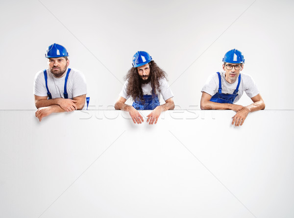 Stock photo: Portrait of a builders leaning on the board
