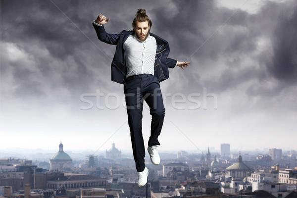 Fashion man jumping to the sky Stock photo © konradbak