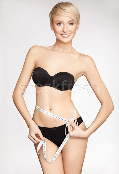 Young beautiful woman with measure tape on white Stock photo © konradbak