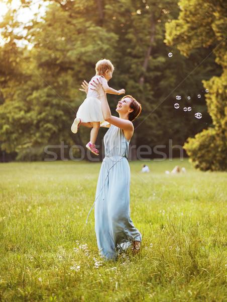 Delighted mother tossing her lovely child Stock photo © konradbak