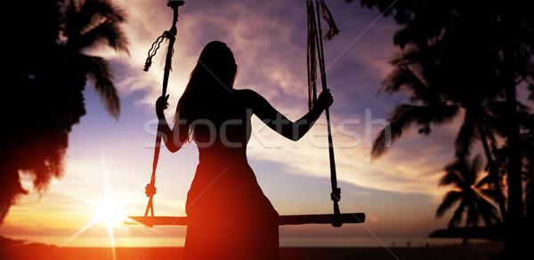 Woman's silhouette sitting on a swing and looking at sunset Stock photo © konradbak
