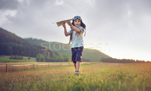 Stock photo: Cute little boy playing toy plane