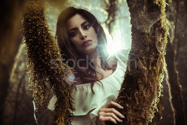 Portrait of a beautoful lady posing among trees Stock photo © konradbak
