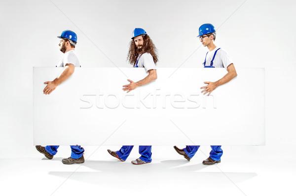 Három jóképű tart üres fehér tábla hordoz Stock fotó © konradbak