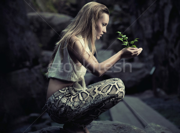 Beautiful young woman holding a plant Stock photo © konradbak