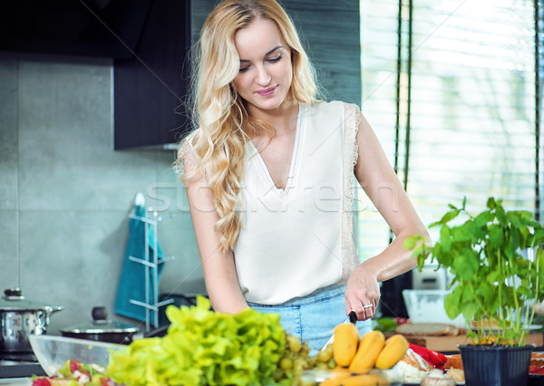 Blonde woman preparing a dinner dish Stock photo © konradbak