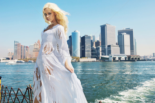 Stock photo: Woman wearing ragged dress with the city in the background