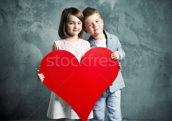 Two kids holding a giant heart Stock photo © konradbak