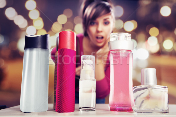 Surprised woman looking at perfumes Stock photo © konradbak