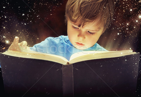 Stock photo: Amazed young boy with magic book