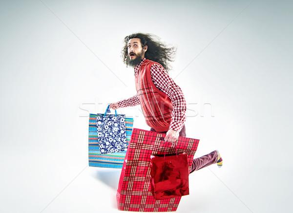 Nerdy guy holding a bunch of shopping bags Stock photo © konradbak