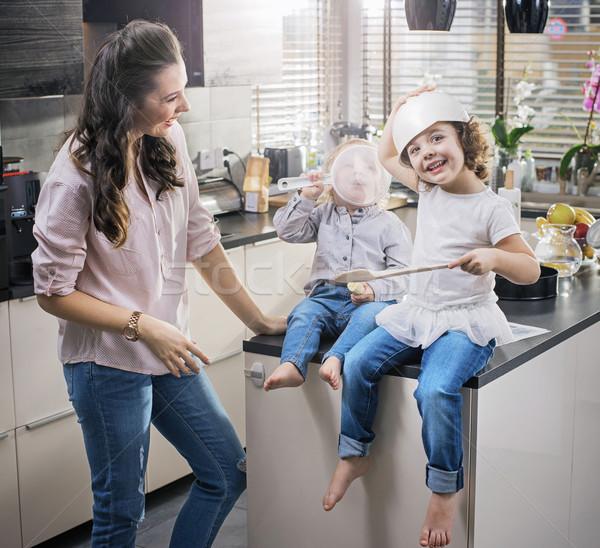 Chherful mom watching her children having fun in the kitchen Stock photo © konradbak