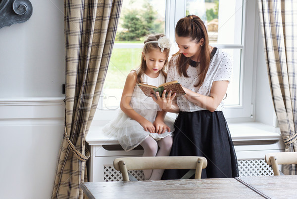 Caring mother teaching daughter how to read Stock photo © konradbak