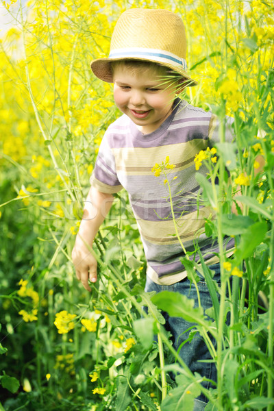 Stock photo: Smiling kid running among the canola flowers