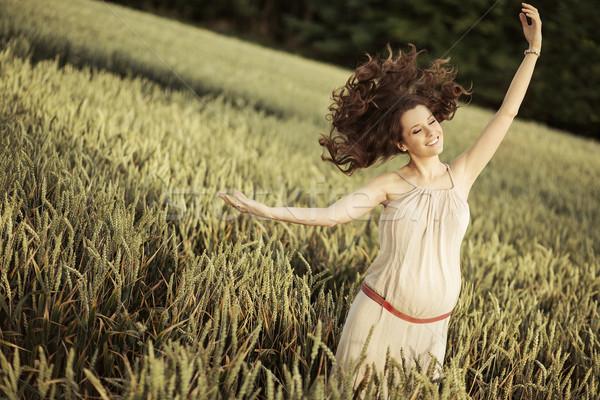 Portrait of the joyful pregnant woman among the cereal crop Stock photo © konradbak