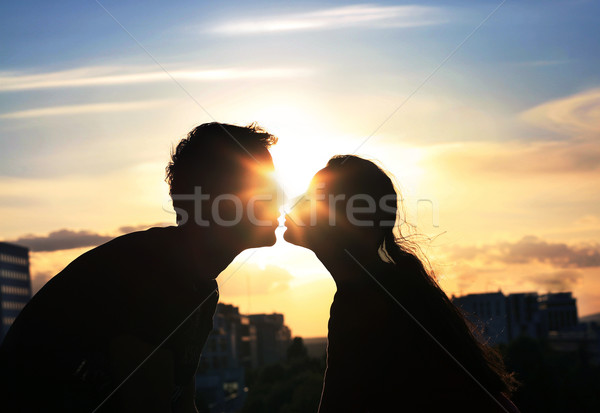 Kissing couple over evening city background Stock photo © konradbak