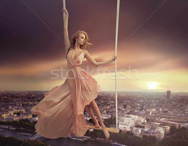 Adorable woman swinging above the city Stock photo © konradbak