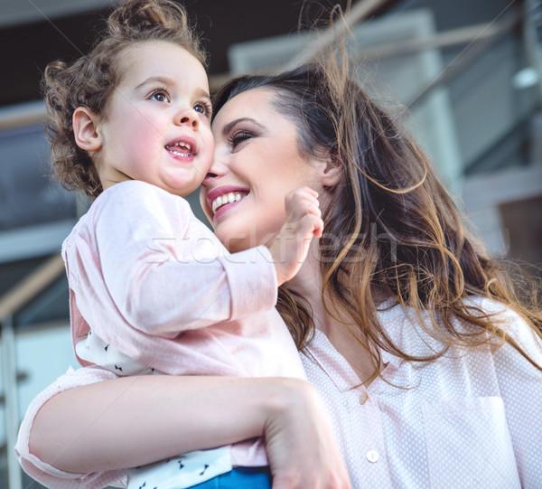 Portrait of a cheerful mom cuddling beloved child Stock photo © konradbak