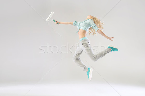 Stock photo: Funny picture of woman holding a roller