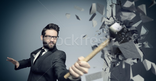 Young boss smashing a wall with a hammer Stock photo © konradbak