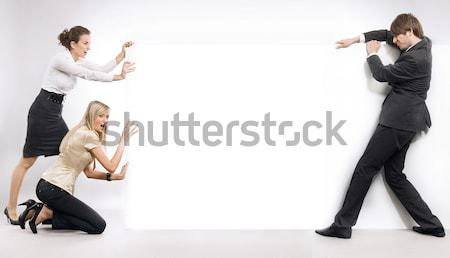 Business people pushing an empty white board Stock photo © konradbak