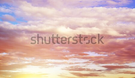 Fluffy clouds floating over the sunset sky Stock photo © konradbak