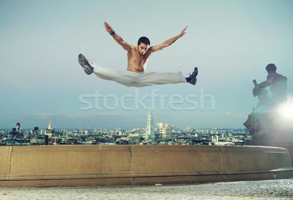 Strong muscular guy doing the splits Stock photo © konradbak