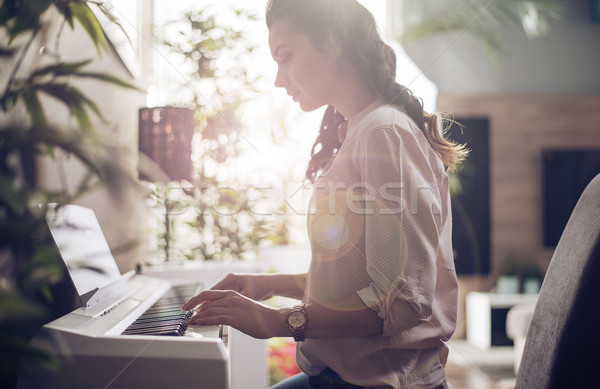 Pretty lady playing the synthesizer Stock photo © konradbak