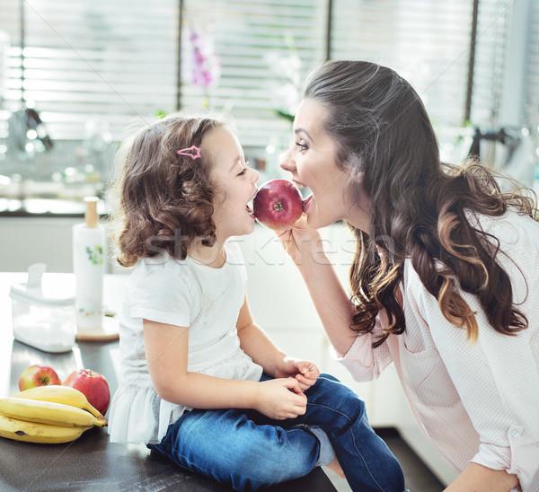 Mother and daughter biting an apple Stock photo © konradbak