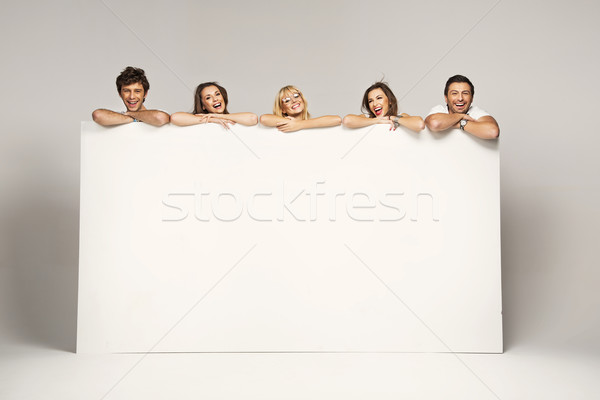 Happy joyful group of friends displaying white placard Stock photo © konradbak