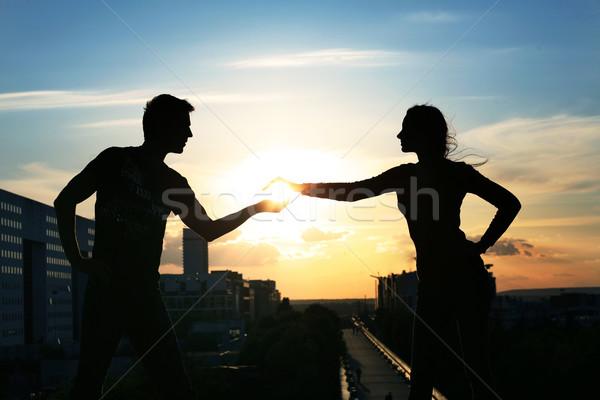 Young couple over evening city background Stock photo © konradbak