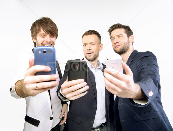A few guys uisng their smart phones Stock photo © konradbak