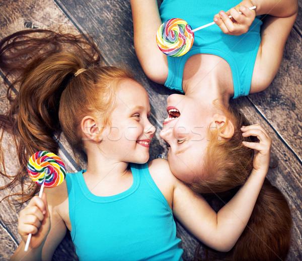 Fine portrait of a twin sisters holding lollipops Stock photo © konradbak