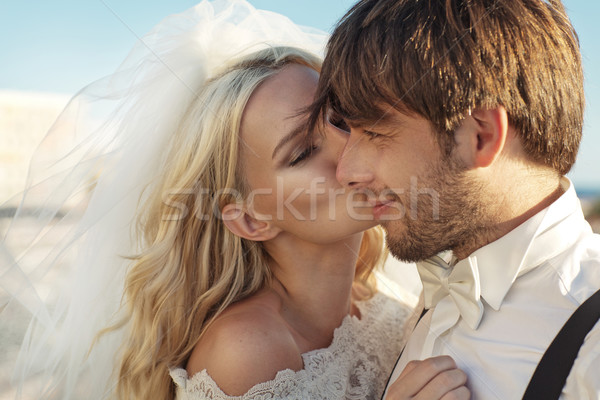 Romantic picture of young bride kissing her husband Stock photo © konradbak