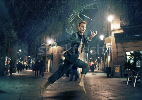 Cheerful young man running during rainy weather Stock photo © konradbak