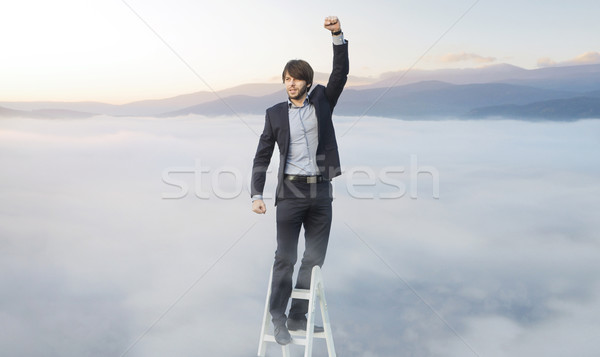 Handsome man on the ladder above the clouds Stock photo © konradbak