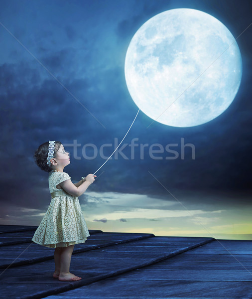 Conceptual image of a baby holding a moon-balloon Stock photo © konradbak