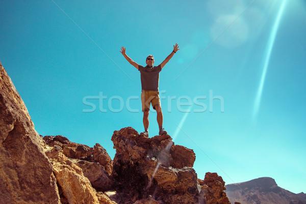 Handsome man standing on the rock Stock photo © konradbak