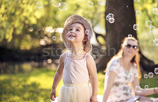 Mother and daughter looking at the soap bubbles Stock photo © konradbak