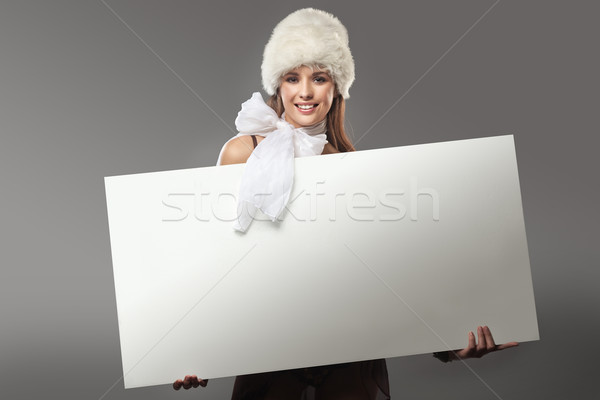 Stock photo: Pretty girl holding a white message board