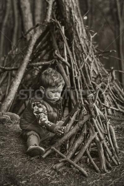 Cute little boy building a wooden hut Stock photo © konradbak