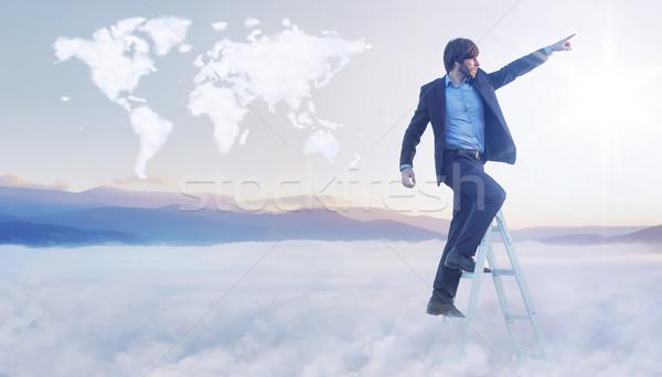 Conceptual image of businessman over the cloud world map Stock photo © konradbak