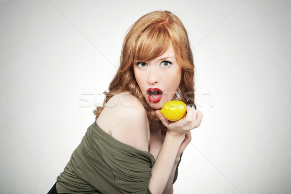 Young red hair woman holding a lemon Stock photo © konradbak