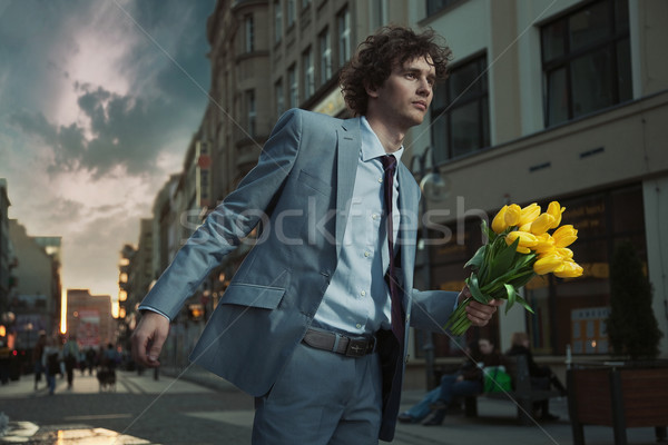 Attractive guy with bunch of tulips Stock photo © konradbak