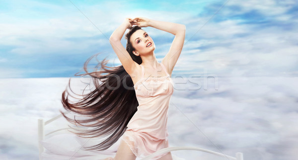 Pretty brunette on heavenly bed Stock photo © konradbak