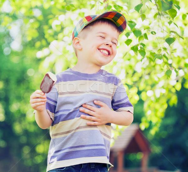 Contented small boy eating an ice cream Stock photo © konradbak