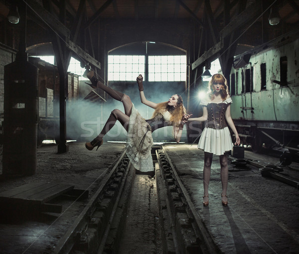 Two witches in the old and empty railway station Stock photo © konradbak