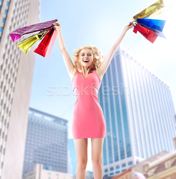 Joyful blond woman jumping with paper bags Stock photo © konradbak